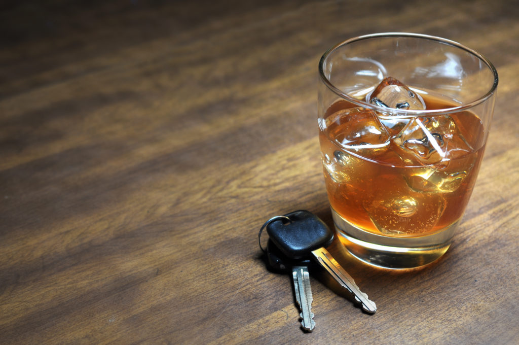 a glass of alcohol on a table next to car keys implying a future DWI charge